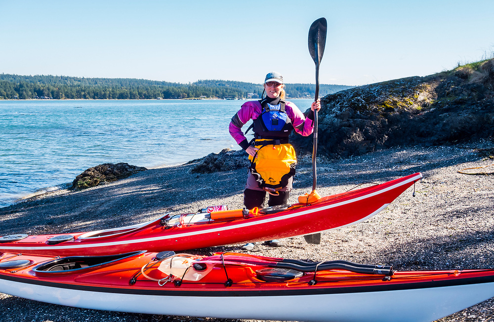 A woman poses for a picture with her sea kayak on Skagit Island, Washington in Skagit Bay, Washington, USA.