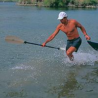 Colorado River, Arizona. Greg Theodore drags kayak off of beach below Hoover Dam.