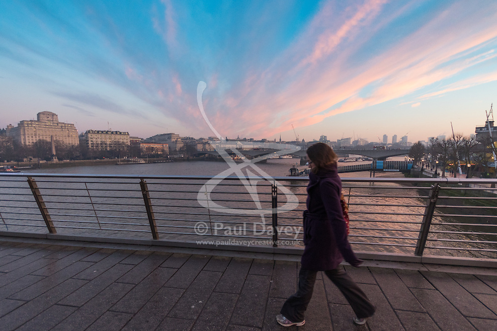 London, January 24th 2017. Photographed from Hungerford Bridge, the early morning light illuminates clouds and buildings of the city's skyline, with the predicted fog failing to appear. High pressure over the UK has caused pollution alerts as fumes are trapped beneath a cold layer of air. PICTURED: A commuter makes her way across Hungerford Bridge.
