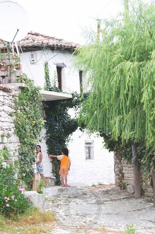 Children on the street in front of white houses. Berat upper citadel old walled city. Albania, Balkan, Europe.