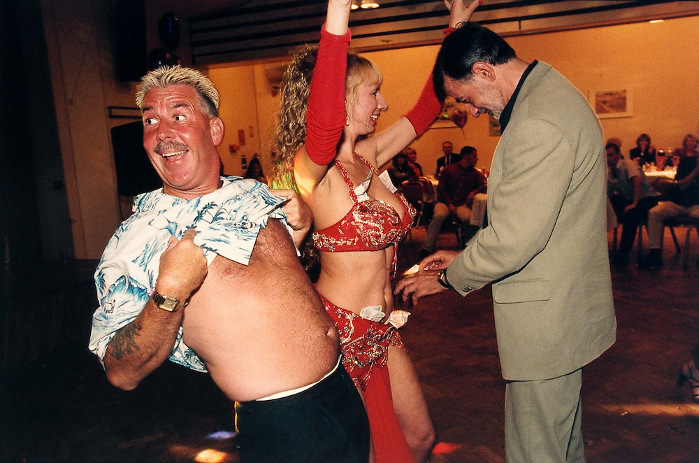 Maria Louisa a belly dancer, dancing at an engagement party in Uxbridge West London. The two men are the are the fathers of bride and groom.