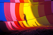 People silhouetted against the inside of a partially inflated envelope at the International Balloon Fiesta, Albuquerque, New Mexico