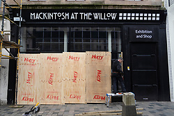 Glasgow, Scotland, UK. 26 March, 2020. Views from city centre in Glasgow on Thursday during the third day of the Government sanctioned Covid-19 lockdown. The city is largely deserted. Only food and convenience stores open. Mackintosh at the Willow shop being boarded up. Pictured; Iain Masterton/Alamy Live News