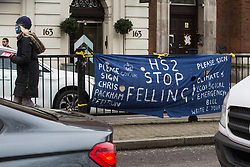 London, UK. 31 January, 2021. A banner hung by anti-HS2 activists on Euston Road calling for HS2 Ltd to stop felling trees in Euston Square Gardens and for members of the public to sign a petition started by Chris Packham. Climbers from the National Eviction Team (NET) are currently dismantling a camp built by activists from HS2 Rebellion, five of whom in tunnels beneath, seeking to protect trees from felling in connection with the controversial HS2 high-speed rail project.