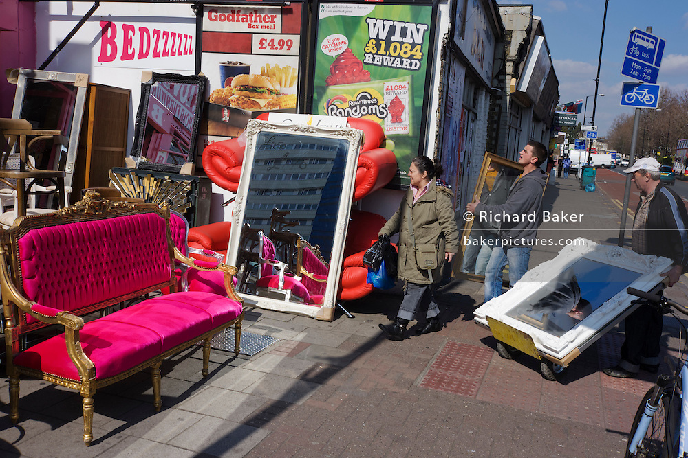 Shop workers deliver new items to accompany other bright furniture on sale in a London street.