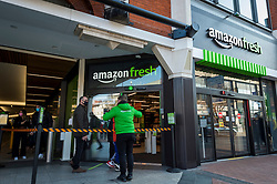 "© Licensed to London News Pictures. 07/03/2021. LONDON, UK.  A staff member manages customers queuing outside the new 2,500 sq ft Amazon Fresh store in Ealing, west London on its first weekend of opening. It is the first ""just walk out"" grocery store in the UK and the first outside the USA.  As a ""contactless"" shop, it is available to anyone signed up to Amazon and with the app on their smartphone.  In-store cameras and artificial intelligence monitor customers picking up items who simply walk out and billing takes place later automatically.  Photo credit: Stephen Chung/LNP"