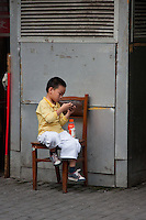 chinese child sitting on a chair in the street in Shanghai China