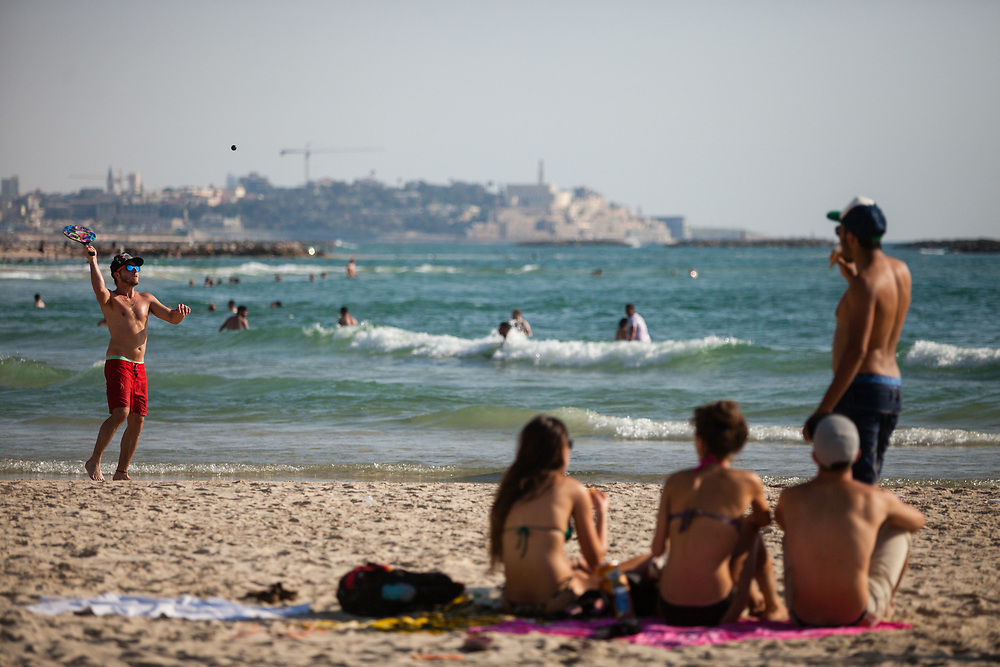 People enjoy a warm summer afternoon and play 'Matkot', or beach paddleball which is often referred to as the country's national sport at Frishman Beach, in Tel Aviv, Israel, on July 21, 2015.