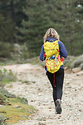 Rear view of hiker walking at Col de Bavella, Corsica, France