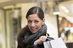 Portrait of a young woman with shopping bag in the shop and smiling, Freiburg im Breisgau, Baden-Wuerttemberg, Germany