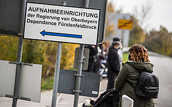 November 3, 2018 - Fuerstenfeldbruck, Bavaria, Germany - A migrant woman with a child walks past the sign for their housing facility in Fuerstenfeldbruck. 100 Migrants at the Fuerstenfeldbruck housing facility near Munich held a rally protesting alleging abuse by security staff and stays lasting two years or more instead of the maximum of six months.  The Fuerstenfeldbruck camp has been a flash point for conflicts for several years, with the predominantly African residents being involved in numerous altercations with security and staff.  Sources state that the migrants housed there have a low perspective to stay or pending deportation orders and such a situation, along with extended stays, leads to conflict. The group Refugee Struggle for Freedom recently released a partial video alleging an attack by several security workers against a resident. Upon return to the camp, an unrelated fight broke out requiring police and medical assistance.  It was at this point that a member of the security team approached a member of the press and aggressively demanded an end to photographing and also attempted to confiscate the cameras and memory cards.  The guard gave up the attempts when the photographer indicated that only the police can give such orders, which they did not. (Credit Image: © Sachelle Babbar/ZUMA Wire)