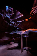 """Sand falls from a ledge in Upper Antelope Canyon on Navajo Nation land near Page, Arizona. Antelope Canyon is a narrow sandstone canyon, known as a slot canyon. Violent flash floods sculpt the sandstone, leaving undulating, layered walls. The Navajo people call the canyon Tsé bighánílíní dóó Hazdistazí, which means """"the place where water runs through rocks."""""""