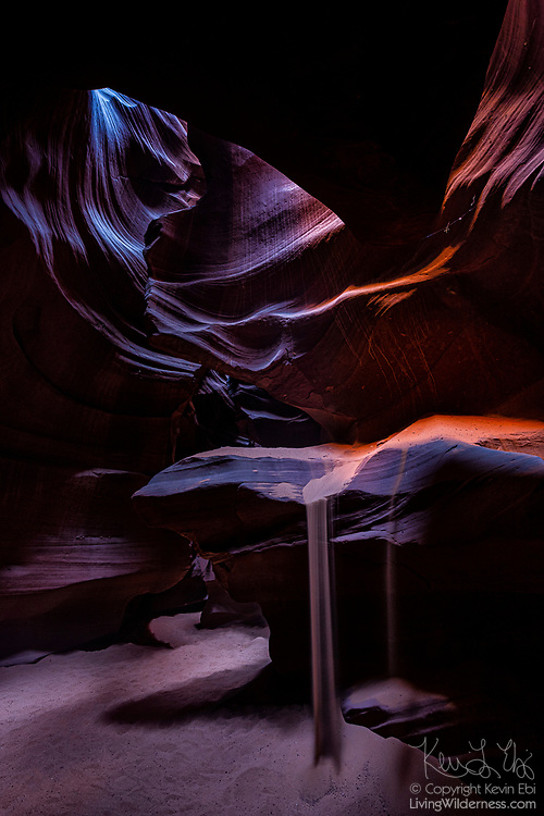 "Sand falls from a ledge in Upper Antelope Canyon on Navajo Nation land near Page, Arizona. Antelope Canyon is a narrow sandstone canyon, known as a slot canyon. Violent flash floods sculpt the sandstone, leaving undulating, layered walls. The Navajo people call the canyon Tsé bighánílíní dóó Hazdistazí, which means ""the place where water runs through rocks."""