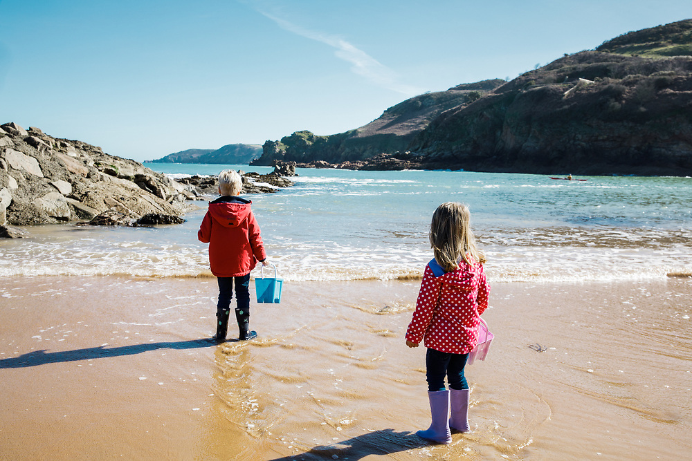 Boy and girl holding buckets and looking out to sea at Greve de L'Ecq beach in Jersey on a sunny day in Spring