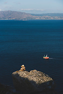 A boat moves through the sea beneath the Cape Finisterre Lighthouse in Galicia, Spain. (July 20, 2018)<br />