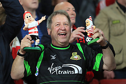 A Doncaster Rovers supporter in the stands holds up garden knomes