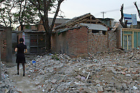 China, Beijing, Chaoyang, San Jian Fang, 2008. A woman heads toward her home through the rubble of businesses demolished to make way for road expansion.