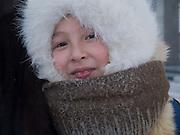 Jakutisches Maedchen mit Kopfbedeckung geschützt gegen die extreme Kaelte in der Innenstadt von Jakutsk. Jakutsk wurde 1632 gegruendet und feierte 2007 sein 375 jaehriges Bestehen. Jakutsk ist im Winter eine der kaeltesten Grossstaedte weltweit mit durchschnittlichen Winter Temperaturen von -40.9 Grad Celsius. Die Stadt ist nicht weit entfernt von Oimjakon, dem Kaeltepol der bewohnten Gebiete der Erde.<br /> <br /> Yakut girl protected with headgears against the extrem climate  in the city center of Yakutsk. Yakutsk was founded in 1632 and celebrated 2007 the 375th anniversary - billboard announcing the celebration. Yakutsk is a city in the Russian Far East, located about 4 degrees (450 km) below the Arctic Circle. It is the capital of the Sakha (Yakutia) Republic (formerly the Yakut Autonomous Soviet Socialist Republic), Russia and a major port on the Lena River. Yakutsk is one of the coldest cities on earth, with winter temperatures averaging -40.9 degrees Celsius.