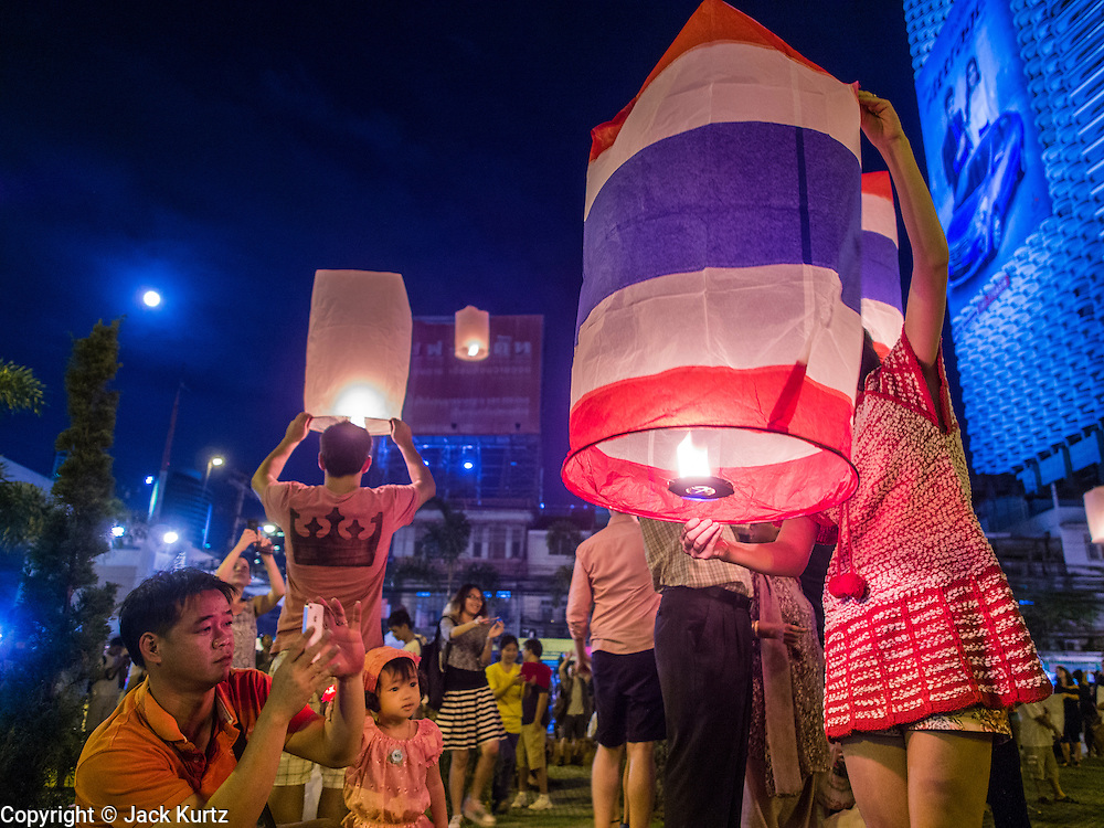 """17 NOVEMBER 2013 - BANGKOK, THAILAND:  People luanch  Yi Peng lanterns on Loy Krathong near Wat Yannawa in Bangkok. The Yi Peng lanterns are Loy Krathong tradition in Chiang Mai but they are becoming more popular  in Bangkok and central Thailand. Loy Krathong (also written as Loi Krathong) is celebrated annually throughout Thailand and certain parts of Laos and Burma (in Shan State). The name could be translated """"Floating Crown"""" or """"Floating Decoration"""" and comes from the tradition of making buoyant decorations which are then floated on a river. Loi Krathong takes place on the evening of the full moon of the 12th month in the traditional and they do this all evening on the 12th month Thai lunar calendar. In the western calendar this usually falls in November. The candle venerates the Buddha with light, while the krathong's floating symbolizes letting go of all one's hatred, anger, and defilements      PHOTO BY JACK KURTZ"""