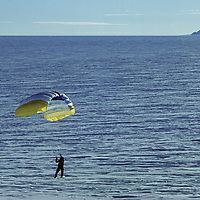 ANTARCTICA. Alejo Contreras Staeding parasails in katabatic winds on polar icecap near Patriot Hills at 80 degrees south latitude. Three Sails nunataks bkg.