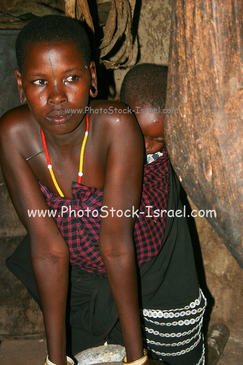 Datoga woman with baby on back mills grain to flour. Photographed in Lake Eyasi Tanzania