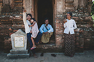 Bagan, Myanmar - November 14, 2011: A Burmese man sits at the entrance to a centuries-old temple where he is a caretaker in Bagan.