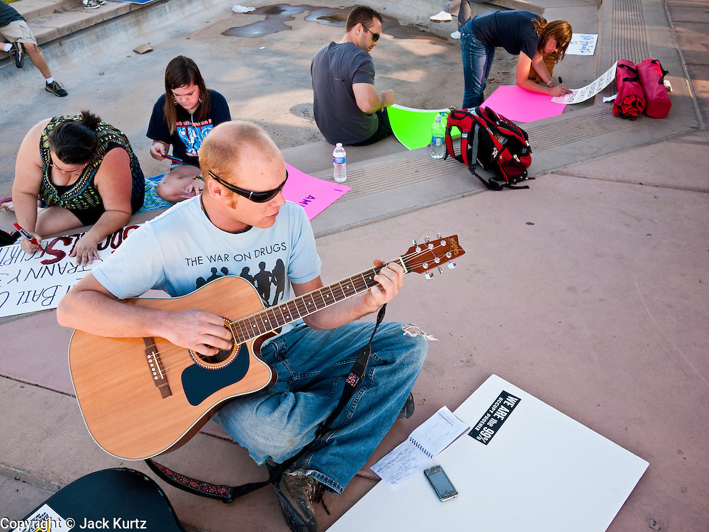 """09 OCTOBER 2011 - PHOENIX, AZ: A man who identified himself as """"Dagger Pan"""" plays guitar while people work on signs for the Occupy Phoenix sign painting party in Phoenix Sunday. About 50 people met in Steele Indian School Park in central Phoenix to paint signs for the Occupy Phoenix demonstration, which is expected to take place on Oct 15. Organizers are expecting more than 1,000 people to come downtown Saturday to protest against big banks and high unemployment.    PHOTO BY JACK KURTZ"""
