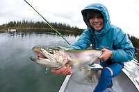 Portrait of young woman and large trout caught while fly fishing unnamed pond near Chilko Lake, BC, Canada