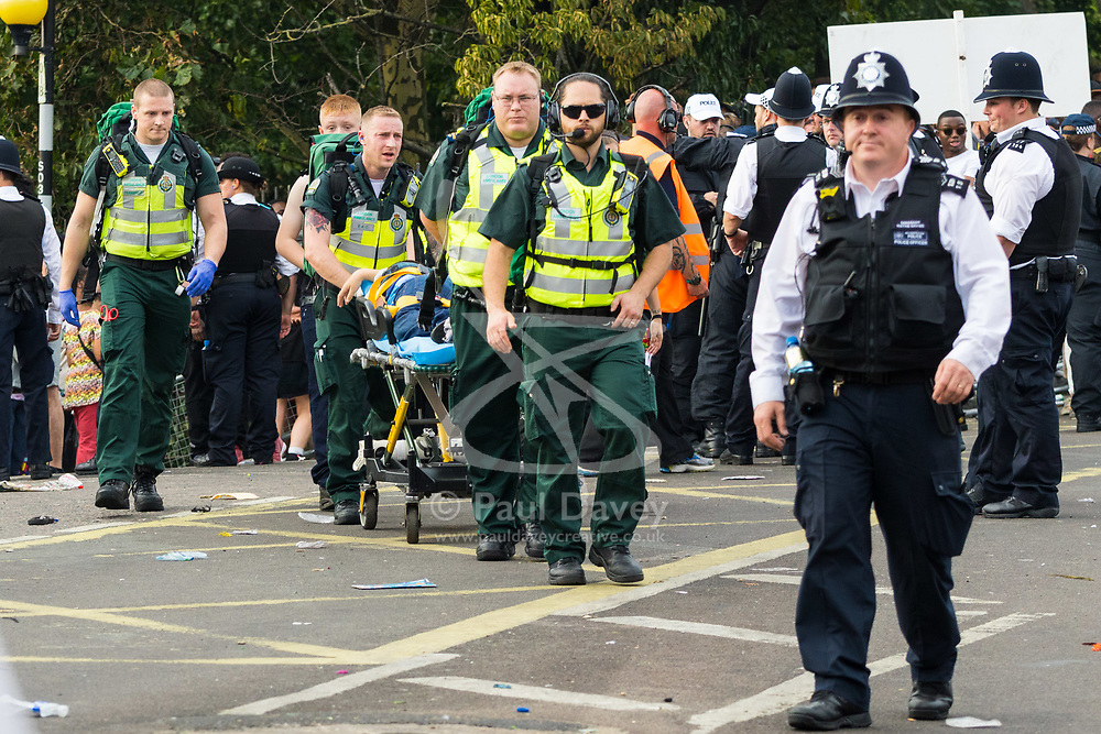 London, August 28 2017. Paramedics stretcher a young boy away on Day Two of the Notting Hill Carnival, Europe's biggest street party held over two days of the August bank holiday weekend, attracting over a million people. © Paul Davey.