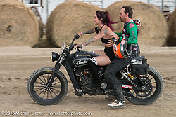 Sarah Furey blasts around the track with Cameron Brewer on back (on his own bike) after the Hooligan Flat Track Racing in front of the main stage at the Buffalo Chip during the annual Sturgis Black Hills Motorcycle Rally. SD, USA. August 10, 2016. Photography ©2016 Michael Lichter.