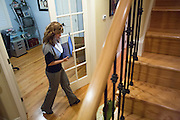 Joy Hahn, Business Development Manager, of Cornerstone Technologies walks from her home office to the kitchen while responding to emails to help her daughter with homework at their home in San Jose, California, on March 25, 2013.  (Stan Olszewski/SOSKIphoto)