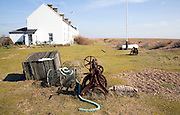 Old rusty fishing winch and lobster pots and Coastguard Cottages, Shingle Street, Suffolk