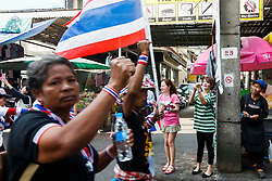 © Licensed to London News Pictures. 20/01/2014. An onlooker takes a photo on her phone as Anti-Government protesters march past in an attempt to shutdown the Government Savings Bank in Bangkok Thailand. Anti-government protesters launch 'Bangkok Shutdown', blocking major intersections in the heart of the capital, as part of their bid to oust the government of Prime Minister Yingluck Shinawatra ahead of elections scheduled to take place on February 2. Photo credit : Asanka Brendon Ratnayake/LNP