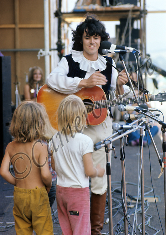 """Donovan amused the audience with a rendition of """"How much of a Pee do you Wee when you're little and only three?"""" he was joined on stage by three small blond boys. Some people joked that they could have been girls, and this apparently greatly amused another artist, Joan Baez who was back stage at the time. - 1970 Isle of Wight Music Festival (displayed as one of 28 images in the slideshow exhibit of Charles Everest's photographs at the V&A)"""
