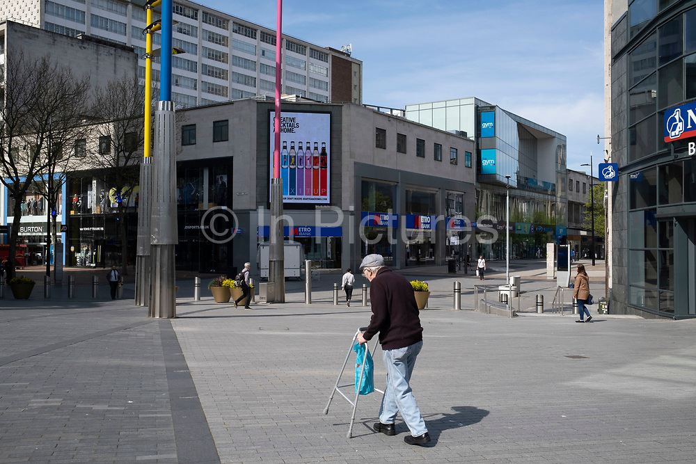 Elderly man struggling, yet succeeding to walk with his zimmer frame after a knee replacement operation at the Bullring and city centre, which is virtually deserted under coronavirus lockdown on 15th April 2020 in Birmingham, England, United Kingdom. Coronavirus or Covid-19 is a new respiratory illness that has not previously been seen in humans. While much or Europe has been placed into lockdown, the UK government has put in place more stringent rules as part of their long term strategy, and in particular social distancing.