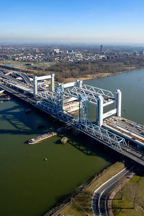 Nederland, Zuid-Holland, Rotterdam, 18-02-2015; bouw van de nieuwe Botlekbrug. De brug over de Oude Maas is een hefbrug, een van de twee brugdelen in geheven toestand. De oude brug met heftorens in de voorgrond, een schip vaart onder de oude brug door.<br /> Construction of the new Botlek bridge. The bridge over the Oude Maas is a vertical-lift bridge or lift bridge, one of the two bridge sections raised. <br /> luchtfoto (toeslag op standard tarieven);<br /> aerial photo (additional fee required);<br /> copyright foto/photo Siebe Swart