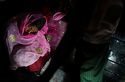 A scared Gora, 13, sits in her home with her sisters the night of her wedding, Rajasthan, India, April 27, 2009. Three young sisters Radha, 15, Gora, 13, and Rajni, 5, were married to their young grooms Aleen, Giniaj and Kaushal, who were also siblings, on the Hindu holy day of Akshaya Tritiya, called Akha Teej in north India. The auspicious day is said to bring good luck to couples married then and is widely known in Rajasthan as the day most child marriages occur. Despite legislation forbidding child marriage in India, such as the Child Marriage Restraint Act-1929 and the much more progressive Prohibition of Child Marriage Act of 2006, marrying children off at a very tender age continues to be accepted by large sections of society.