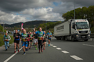 """People run on the 20th Korrika.  Irun (Basque Country). April 4, 2017. The """"Korrika"""" is a relay course, with a wooden baton that passes from hand to hand without interruption, organised every two years in a bid to promote the basque language. The Korrika runs over 11 days and 10 nights, crossing many Basque villages and cities. This year was the 20th edition and run more than 2500 Kilometres. Some people consider it an honour to carry the baton with the symbol of the Basques, """"buying"""" kilometres to support Basque language teaching. (Gari Garaialde / Bostok Photo)"""