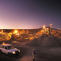 Mine plant area and stockpile at dusk<br /> Process engineer on two way radio