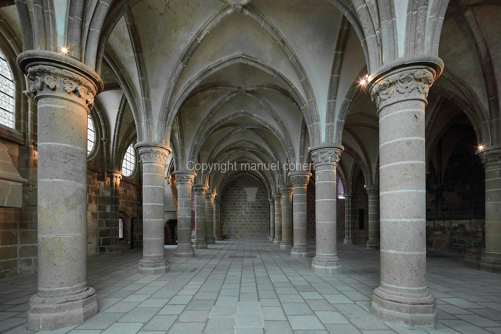 The Scriptorium, built 1215-20, renamed the Salle des Chevaliers or Knights Chamber in the 15th century when King Louis XI founded the Order of the Knights of Saint Michel, in the Merveille, built 1203-28, to the North of the Abbey Church, built with a donation from the King of France, Philip Augustus, at Mont-Saint-Michel or St Michael's Mount, a tidal island housing a Benedictine abbey founded in 966, and other medieval buildings within strong defensive ramparts, Normandy, Northern France. The room is Norman in style, with 3 rows of columns with carved capitals, a cross vaulted ceiling, windows and 2 fireplaces. Mont-Saint-Michel is listed as a UNESCO World Heritage Site and its abbey and many other buildings are historic monuments. Picture by Manuel Cohen