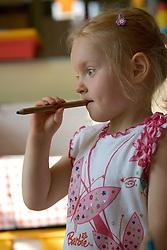 Girl in nursery school; deep in thought,