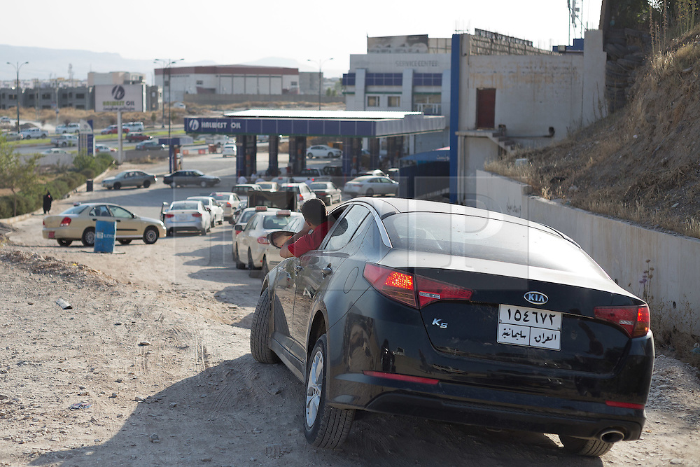 © Licensed to London News Pictures. 26/06/2014. Sulaimaniyah, Iraq. Iraqi drivers queue for fuel at a petrol station in Sulaimaniyah, Iraqi-Kurdistan. Despite being an oil-rich country Iraq's main oil refinery at Baiji is now the hands of ISIS insurgents cutting much of the fuel to the rest of the country. Petrol rationing has come in to force across northern Iraq with huge queues that mean many drivers wait in line for hours, sometimes overnight, just to receive their allowance of 30 litres. The shortage has also seen a huge increase in fuel prices with a litre of petrol rising 150% from 500 Iraqi Dinars to 1500 Iraqi Dinars. Photo credit: Matt Cetti-Roberts/LNP