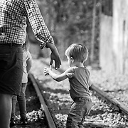 Father helping a chid cross a railtrack