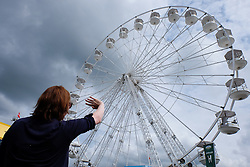 © Licensed to London News Pictures.14/07/15<br /> Harrogate, UK. <br /> <br /> A woman waves to a family member on a ride during the opening day of the Great Yorkshire Show.  <br /> <br /> England's premier agricultural show opened it's gates today for the start of three days of showcasing the best in British farming and the countryside.<br /> <br /> The event, which attracts over 130,000 visitors each year displays the cream of the country's livestock and offers numerous displays and events giving the chance for visitors to see many different countryside activities.<br /> <br /> Photo credit : Ian Forsyth/LNP