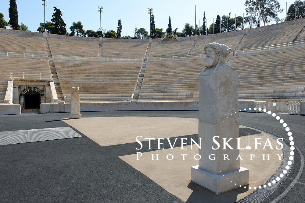 Athens. Greece. View of the two side distinctive herms (ancient stone carved head or bust) located at the curved end of the stadium. The stone sculpture depicts two male figures, one young male figure is facing towards the grandstand, and the other an older beared male figure is facing the track. The Panathenaic (Kallimarmaro) stadium was used for the first international Olympic games of the modern era in 1896.  The completely marble stadium occupies the exact site of the original, built in 330BC which was used for the ancient Panathenaic games (part of the larger religious festival, the Panathenaia).