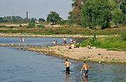Nederland, nijmegen, 25-8-2019 Mensen zoeken verkoeling aan de oevers van de waal op deze tropisch warme nazomerdag .Het is verboden in de rivier te zwemmen vanwege de stroming het het drukken scheepvaartverkeer    .Foto: Flip Franssen