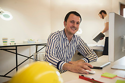 Architect working on computer and smiling in office, Bavaria, Germany