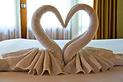 Towels arranged as swans on the bed in guest's room. Photographed in Southeast Asia, Thailand, Koh Chang resort Hotel
