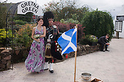 Family stands with Scottish piper at Gretna Green, where Britain's wedding couples converge on for a quickie marriage.