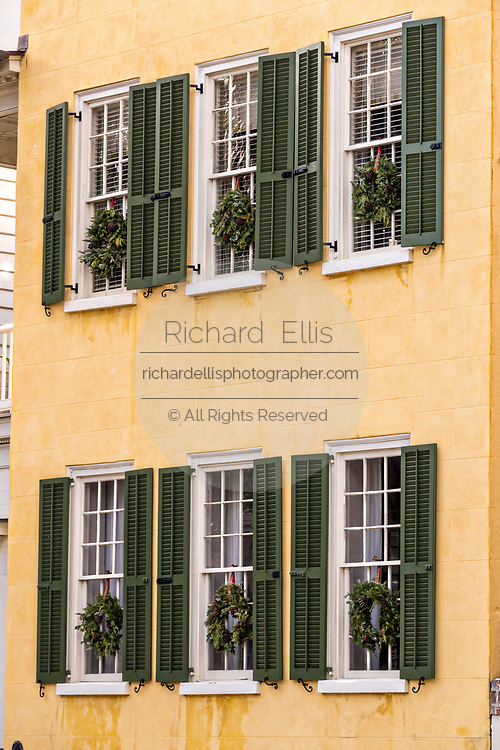 Evergreen Christmas wreaths decorates the windows of a historic home at Meeting Street in Charleston, South Carolina.